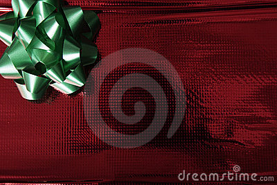 Shiny red wrapping paper with green bow