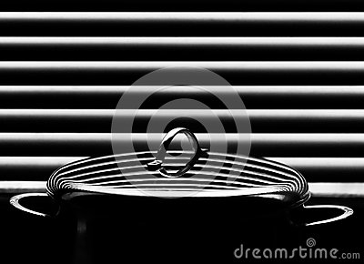 Shiny stainless saucepan with cover on the abstract background