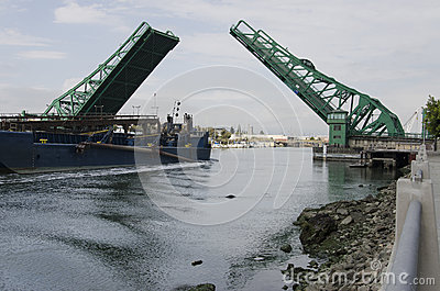 Ship Passing Under a Raised Green Drawbridge