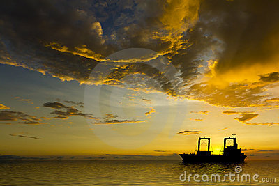 Ship Silhouette with Stormy Clouds at Sunset