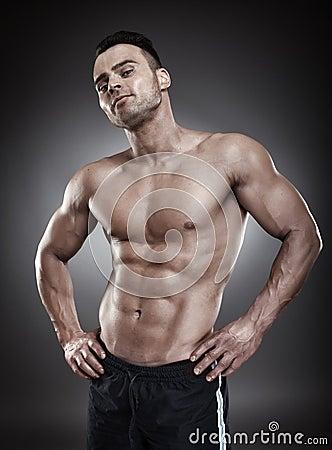Shirtless athletic man standing akimbo