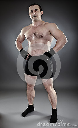 Shirtless athletic muscular man standing akimbo