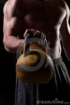 Shirtless guy holding a dumbbell