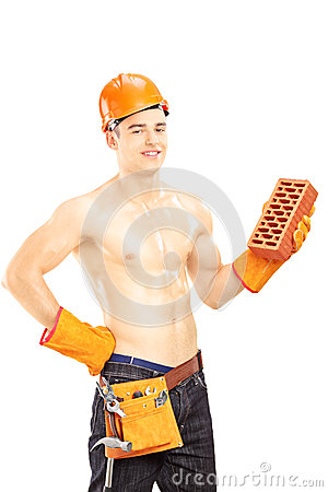 Shirtless male construction worker with helmet holding brick