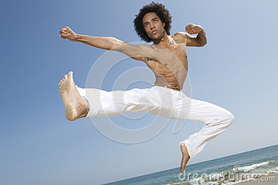 Shirtless Man Jumping On Beach