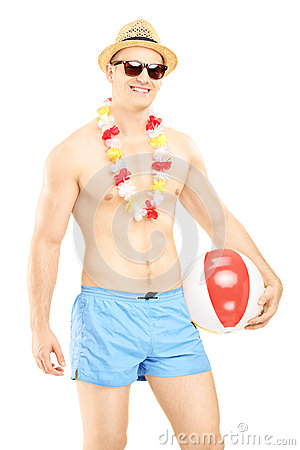 Shirtless man in swimming shorts, holding a beach ball