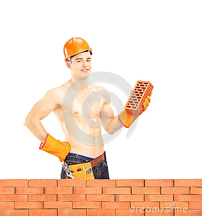 Shirtless muscular male construction worker holding a brick