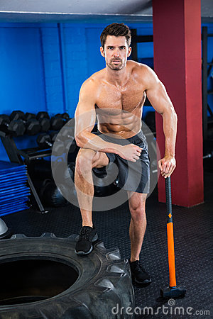 Free Shirtless Young Athlete With Sledgehammer In Gym Stock Photos - 78640163