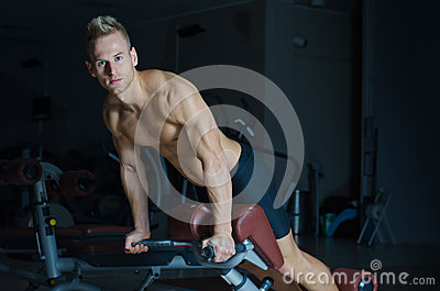 Shirtless young man exercising femural biceps on gym equipment