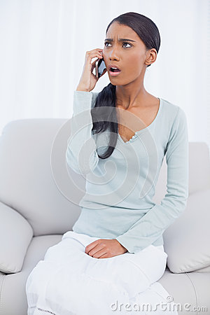 Shocked attractive woman sitting on cosy sofa having a phone cal