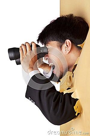 Shocked businessman looking with binoculars