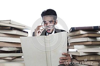 Shocked businessman reading books