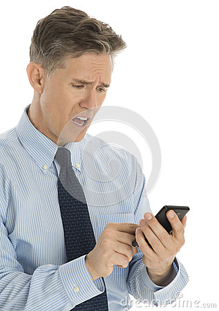 Shocked Businessman Text Messaging Through Smart Phone