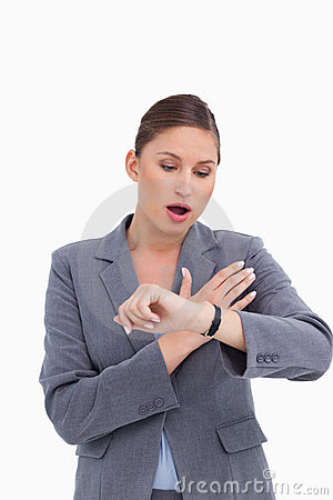 Shocked businesswoman looking at her watch