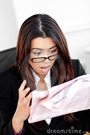 Shocked businesswoman reading a newspaper
