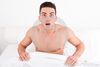 Shocked half naked young man in bed  looking down at his underwe