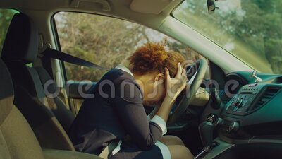 Shocked female driver committing traffic accident. Shocked helpless attractive african american female driver in stylish clothes with head on steering wheel stock video footage