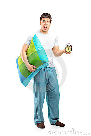 Shocked male holding a pillow and alarm clock