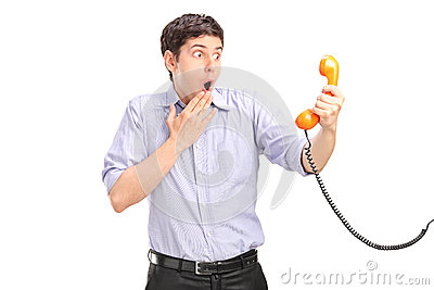 A shocked man holding a telephone tube