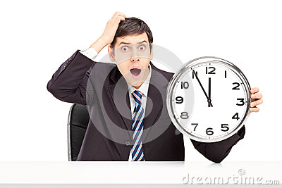 Shocked man in a suit, sitting and holding a clock