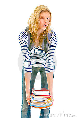 Shocked teen girl holding heavy pile of books