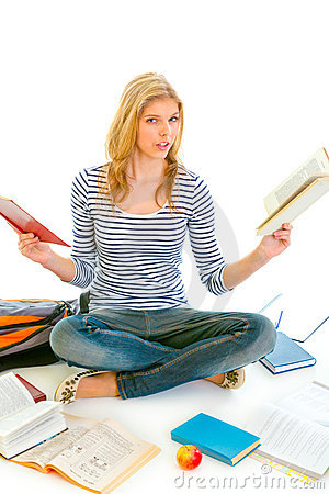 Shocked teen girl sitting on floor with books