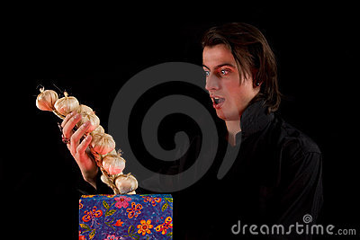 Shocked vampire with gift box taking out garlic
