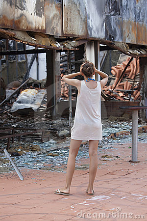 Shocked woman and burned out house