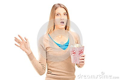 Shocked woman holding a box of popcorn