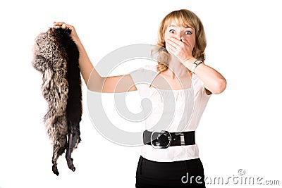 Shocked woman holding fur skin