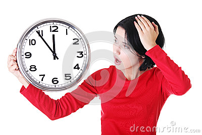 Shocked woman holding office clock