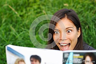 Shocked woman reading magazine