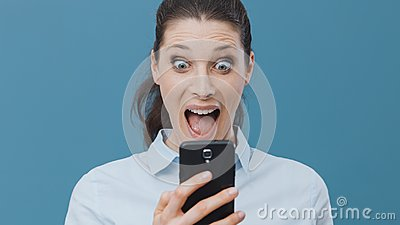 Shocked woman using a smartphone and connecting Stock Photo
