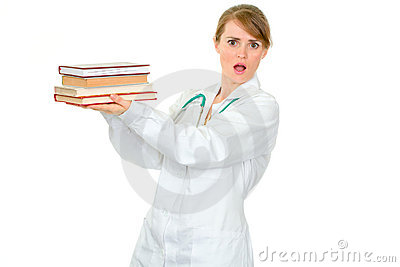 Shocked young female doctor holding medical books