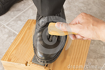Shoe shiner brushing a businessman shoe