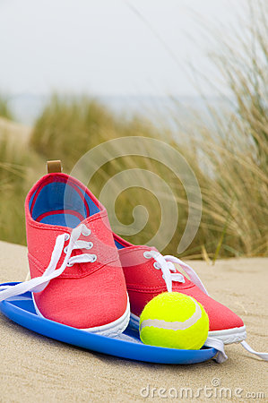 Shoes, ball and frisbee on beach