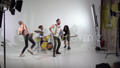 Shooting a clip of a punk rock band. A videographer is working. The musicians are jumping with instruments. The bass. Shooting a clip of a punk rock band. A stock footage