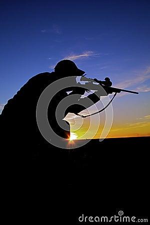 Shooting del cazador del rifle en la salida del sol
