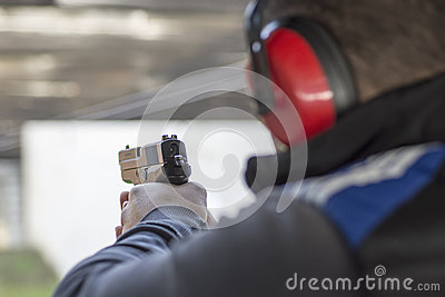 Shooting with Gun at Target in Shooting Range. Man Practicing Fire Pistol Shooting. Stock Photo