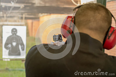Shooting with a pistol. Man Firing pistol in shooting range. Stock Photo