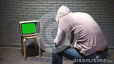 Shooting van de mens in hoodie naar retro tv kijkt stock video
