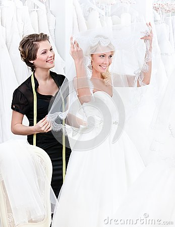 Shop assistant helps to the bride to put the weddi