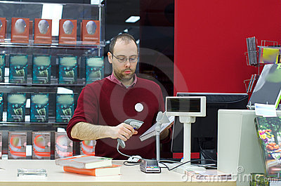 Shop assistant male scanning a book