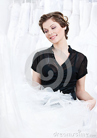 Shop assistant selects a proper dress