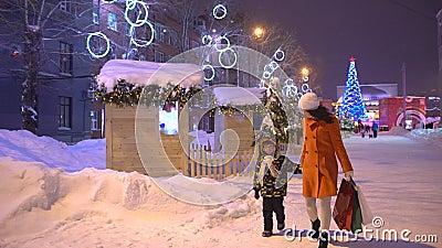 shoppa för jul xmas Jul semestrar shoppare på natten, den upptagna stadsgatan för kors, ultrarapidmodern och hennes son lager videofilmer