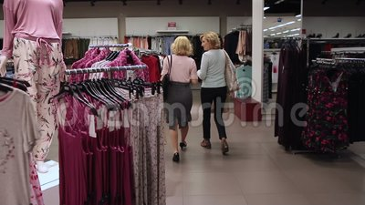 Shopper women selecting clothes in clothing shop stock footage