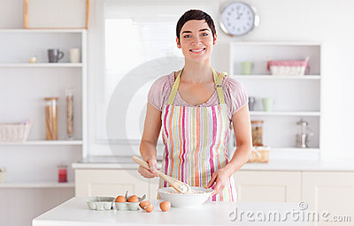 Short-haired brunette woman preparing a cake