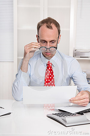 Short sighted at work - balding businessman looking through glas
