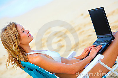 Shot of a Beautiful Young Woman on the Beach with Laptop