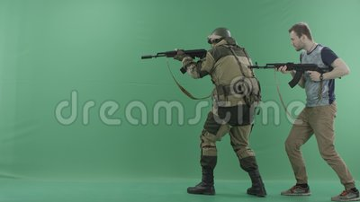 Civilian with machine gun caughts terrorist in military uniform with a  weapon against chromakey background